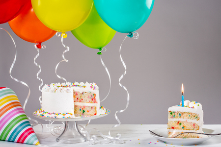 White Buttercream birthday cake with colorful balloons and hat. Stock Photo