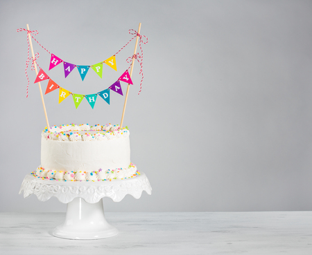 pastel de cumpleaños: Blanco crema de mantequilla tarta de cumpleaños con coloridos banderines y rocía sobre el fondo blanco Foto de archivo