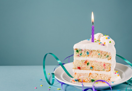 porcion de torta: Rebanada de pastel de cumpleaños con una vela encendida y cintas sobre un fondo azul.