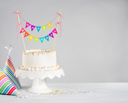 White Buttercream birthday cake with colorful bunting and party hats over white background