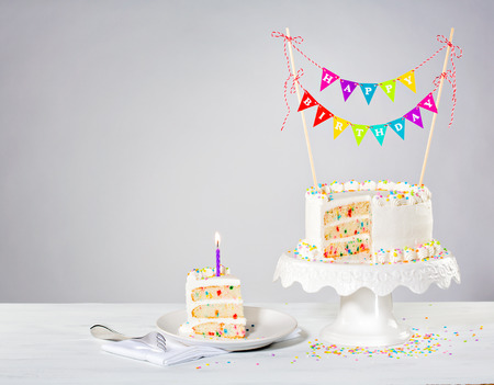 Confetti Buttercream birthday cake with colorful bunting and sprinkles over white background Foto de archivo
