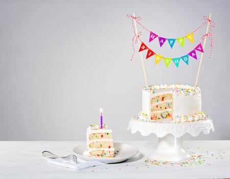 rebanada de pastel: Confetti crema de mantequilla tarta de cumpleaños con coloridos banderines y rocía sobre el fondo blanco