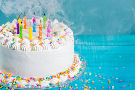White Buttercream icing birthday cake with blown out Candles over blue background
