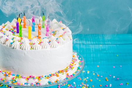 pastel de cumpleaños: Blanco crema de mantequilla glaseado de la torta de cumpleaños con velas sopladas hacia fuera sobre fondo azul Foto de archivo