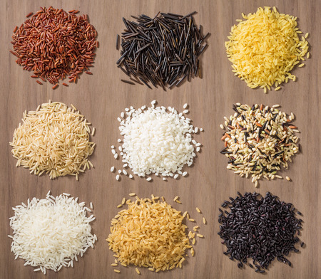 jasmine rice: Piles of different rice varieties over a wooden background including jasmine, basmati, wild rice, risotto and parboiled in Red, white, brown and black.