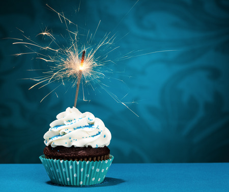 Cupcake with sprinkles and  a sparkler over a blue background.