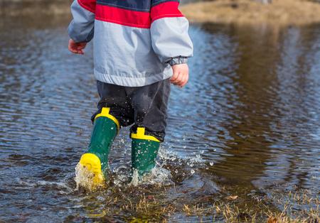 child boy: Very wet little boy strolling through puddles wearing rainboots.