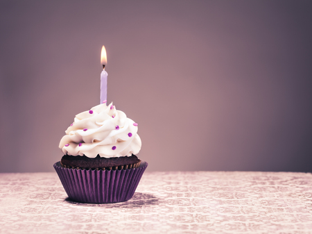 butter icing: Chocolate Cupcake with butter cream icing, purple liner and lit birthday candle.