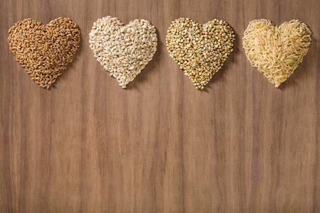Gesunde Vollkornprodukte geformt wie Herzen über einem hölzernen Hintergrund. Weizen, Gerste, Buchweizen und brauner Reis. Standard-Bild - 57170091