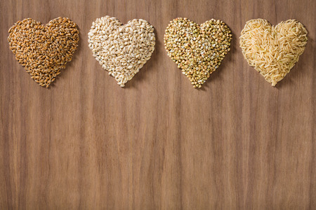 Healthy whole grains shaped like hearts over a wooden background. Wheat, barley, buckwheat and brown rice. Banco de Imagens