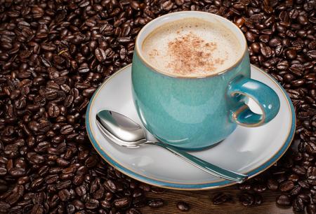 capuchino: Café Latte en una taza azul con los granos