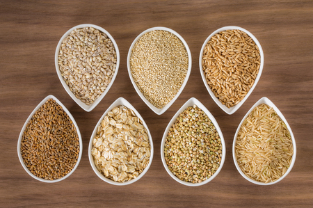 grains: An assortment of whole grains in bowls over a wooden background