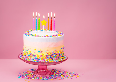cake birthday: Colorful Birthday cake with sprinkles over a pink background.
