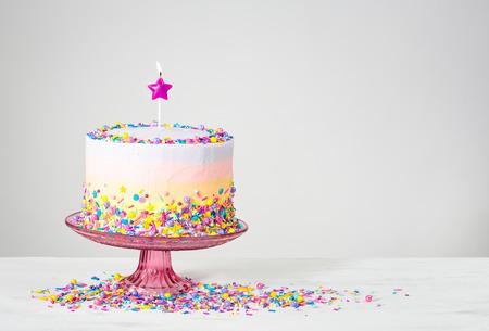 Geburtstagstorte mit Stern Kerze und bunten Streuseln Standard-Bild - 62543116