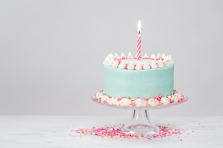 hundreds and thousands: Pastel blue birthday cake over white background with pink sprinkles.
