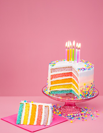 Colorful rainbow Birthday cake with candles over a pink background. Standard-Bild