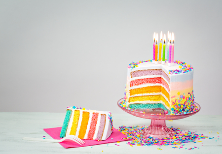 Colorful rainbow layered Birthday cake with lit candles and sprinkles Archivio Fotografico