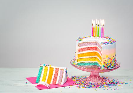 rebanada de pastel: Torta de cumpleaños del arco iris en capas de colores con velas encendidas y rocía Foto de archivo