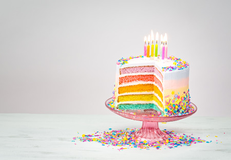 hundreds: Colorful rainbow layered Birthday cake with lit candles and sprinkles Stock Photo