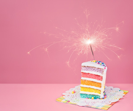 one year: Slice of  birthday cake on a pink background with rainbow layers and sparkler. Stock Photo
