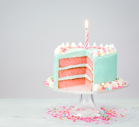 hundreds and thousands: Pastel blue birthday cake over white background with pink layers and sprinkles.
