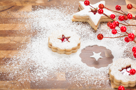 Christmas Linzer Cookies with powdered sugar on a wooden background.