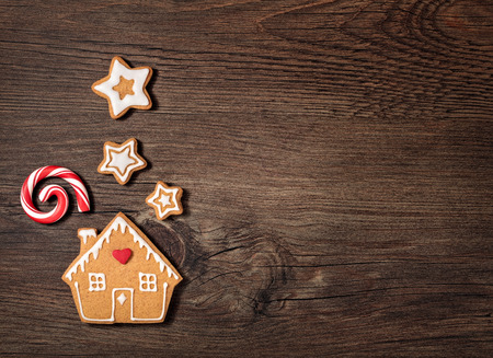 Gingerbread House cookie with candy cane chimney smoke and stars or snow over a wooden background. Foto de archivo