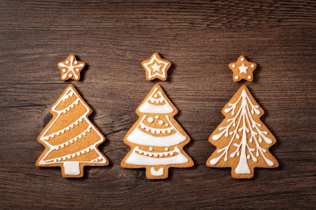 topper: Three Christmas tree cookies with star toppers on wooden background.