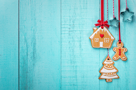 Gingerbread Man, house and tree cookies hanging with ribbin over a blue background