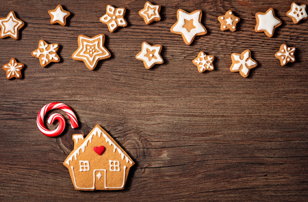 Gingerbread House cookie with candy cane and stars over a wooden background. Banque d'images