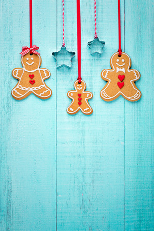 Happy Gingerbread family hanging border on blue background.