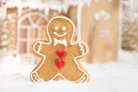 galleta de jengibre: Gingerbread man cookie standing in front of a gingerbread house.