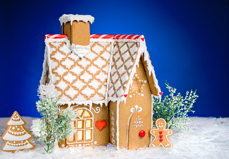 gingerbread: Homemade gingerbread house scene on blue background Stock Photo