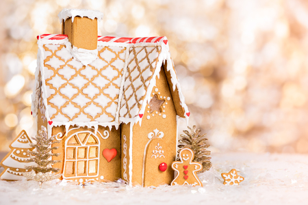 Homemade gingerbread house scene on warm bokeh background