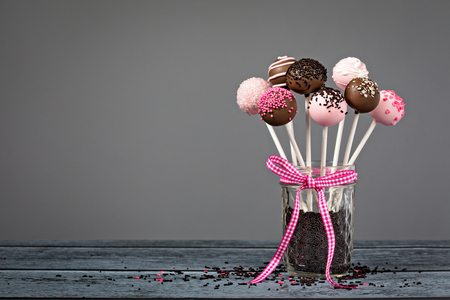 Assortment of chocolate cake pops in a jar with a cute pink bow over a grey background.