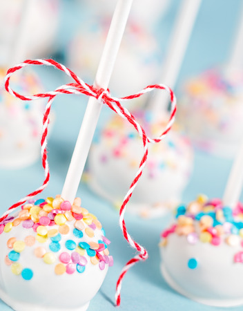 Vanilla cake pops with colorful sprinkles and red bow over a blue background.