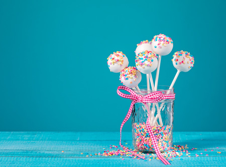 Vanilla cake pops with colorful sprinkles in a cute jar over a blue background.