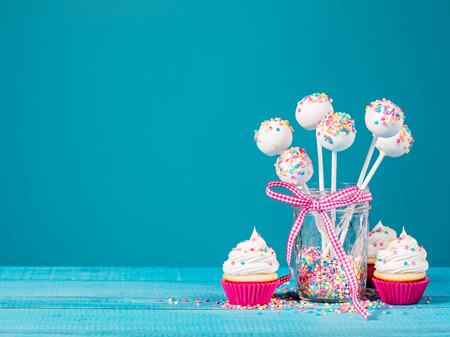 Vanilla cake pops with colorful sprinkles and cupcakes on a blue background.