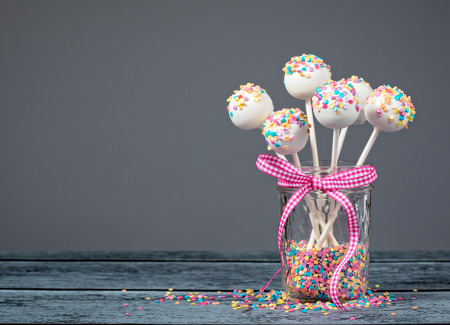 Vanilla cake pops with sprinkles and a cute pink bow over a grey background.
