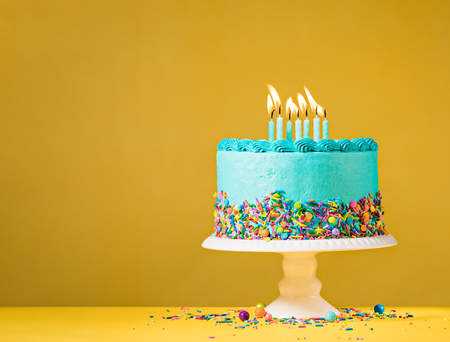 hundreds and thousands: Blue buttercream birthday cake with colorful sprinkles over yellow background.