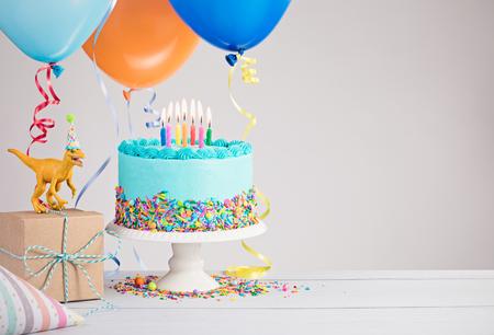 Childs verjaardagsfeest scene met blauwe taart, cadeau doos, speelgoed dinosaurus, hoeden en kleurrijke ballonnen over lichtgrijs.
