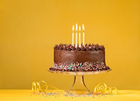 Gâteau d'anniversaire au chocolat avec des paillettes colorées et des bougies sur fond jaune.