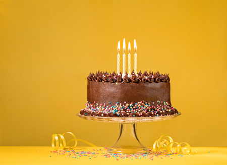 Chocolate birthday cake with colorful sprinkles and candles over yellow background.