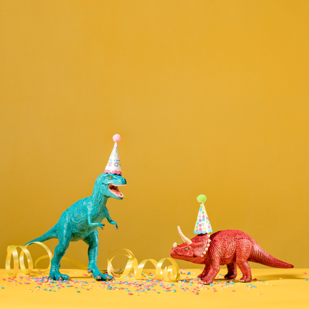 Two dinosaurs with birthday hats partying on a yellow background.