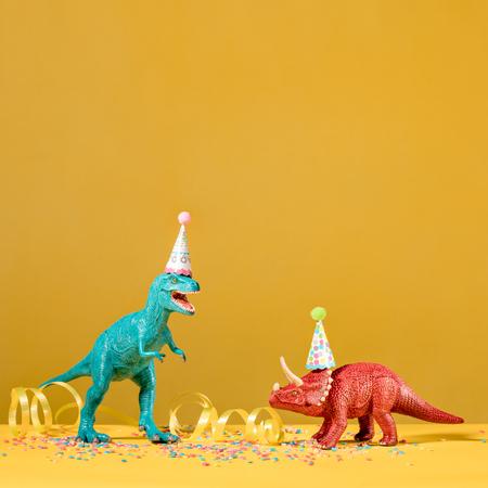 Zwei Dinosaurier mit Geburtstagshüte partying auf einem gelben Hintergrund. Standard-Bild - 78947348