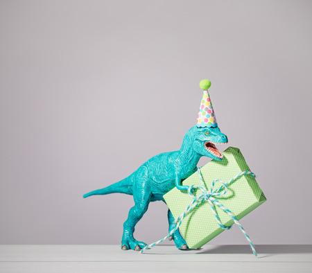 party hat: T-rex dinosaur toy with birthday hat holding gift on a light grey background.