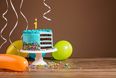 Tort urodzinowy z niebieskim pudrem buttercream i kolorowe balony i świeczką numer 1.