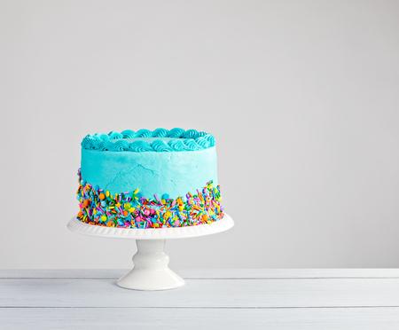 明るい灰色の背景にカラフルな振りかけると青い buttercream ケーキ。 写真素材