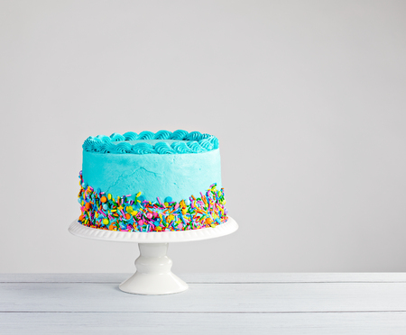 Blue buttercream cake with colorful sprinkles over a light grey background. Foto de archivo