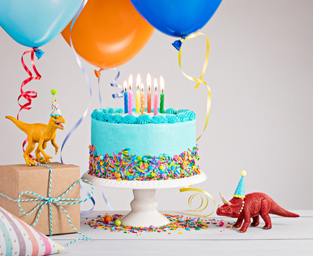 Childs birthday party scene with blue cake, gift box, toy dinosaurs, hats and colorful balloons over light grey.
